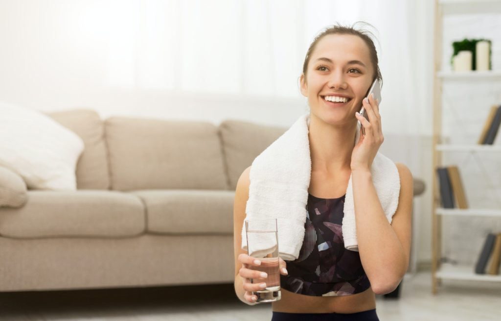 Rest after home workout. Woman talking on phone